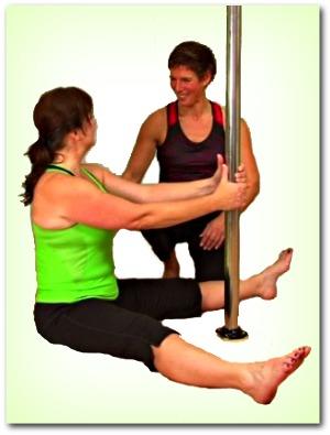 pole dance teacher helping student