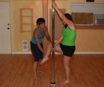 teacher and student learning to pole dance
