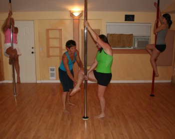 Teacher and students in a group pole dancing class